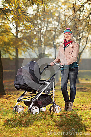 A smiling mother posing with a baby stroller