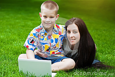 Smiling Mother and son laying on grass with laptop