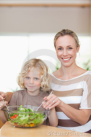 Smiling mother and son stirring salad