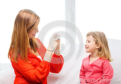 Smiling mother taking picture of daughter