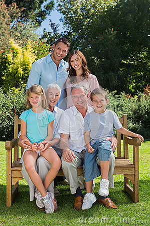 Smiling multi generation family sitting on a bench in park