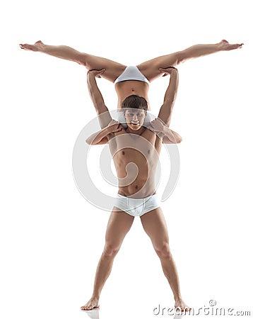 Smiling muscular acrobat holds partner
