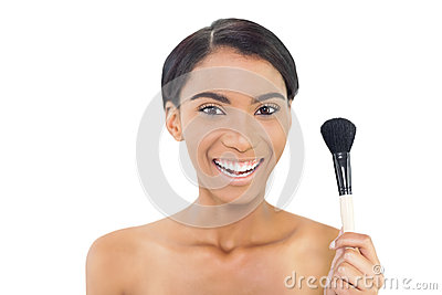 Smiling natural model holding blusher brush