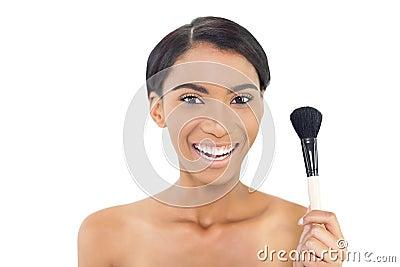 Smiling natural model holding blusher brush