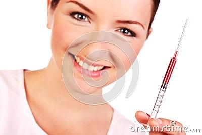 Smiling nurse holding up syringe of blood