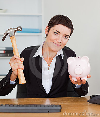 Smiling office worker breaking a piggy bank