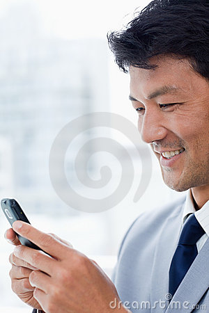 A smiling office worker using his mobile phone