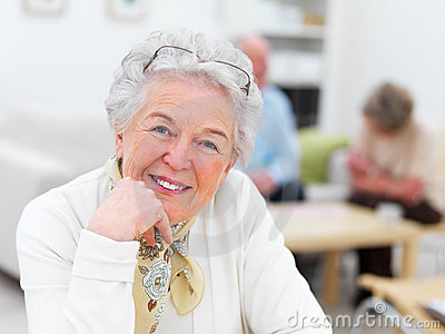 Smiling old woman with people in the background