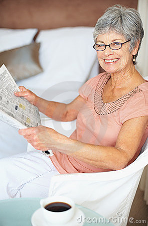 A smiling old woman reading newspaper at home