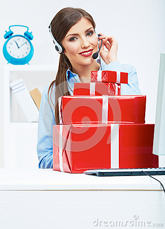 Smiling operator seat at table with red gift box. Happy busines