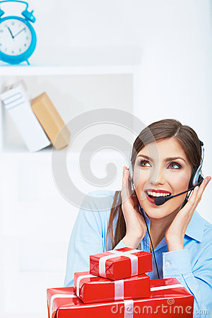 Smiling operator seat at table with red gift box.