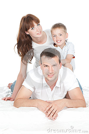 Smiling parents with little son lying on white bed