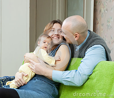 Smiling parents with newborn in home