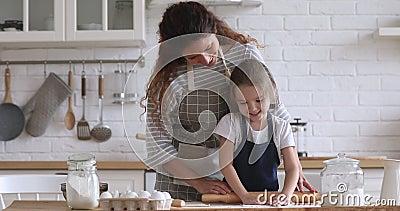 Smiling pleasant young mother and little preschool daughter preparing dough. Smiling pleasant young mother and little preschool daughter in aprons preparing stock video