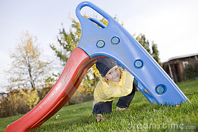 Smiling positive child sit under slide on grass