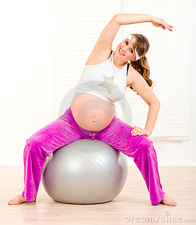 Smiling pregnant woman doing exercises on ball