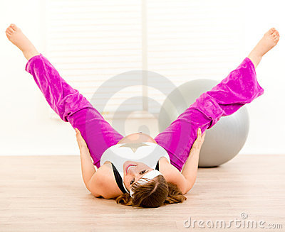 Smiling pregnant woman doing stretching exercises