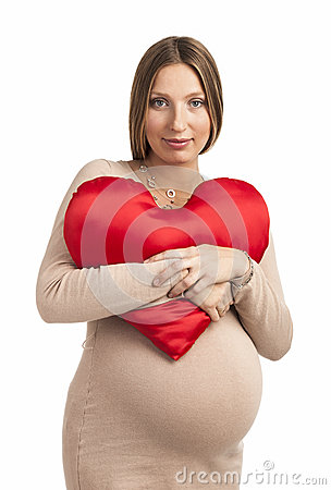 Smiling pregnant woman with heart shaped pillow