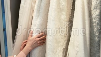 Smiling pretty bride chooses wedding gown at bridal boutique.  stock footage