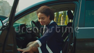 Smiling pretty female driver opening car door. Positive attractive african female driver in trendy clothes opening car door during road trip and looking with stock video footage