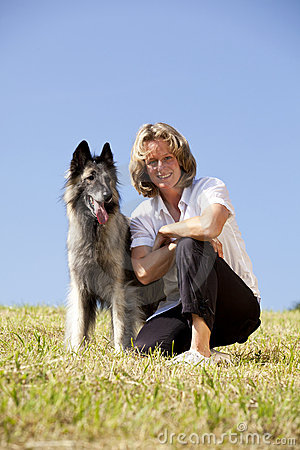 Smiling and proud woman with Belgian shepherd