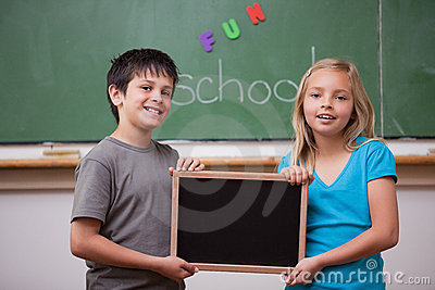 Smiling pupils holding a school slate