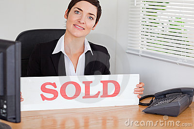 Smiling real estate agent with a sold panel