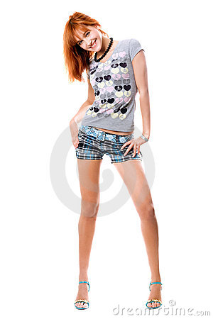 Smiling red-haired girl in a t-shirt and shorts
