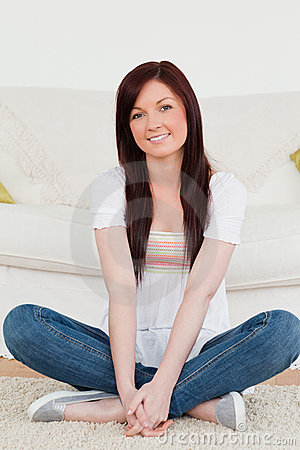 Smiling red-haired woman posing while sitting