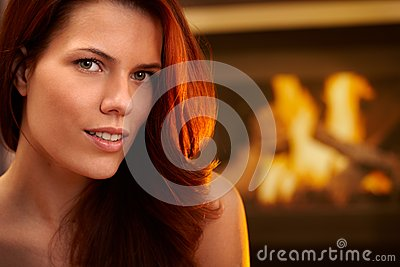 Smiling redhead beauty in front of fireplace