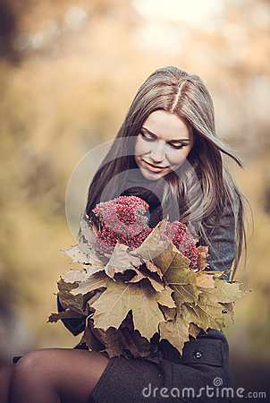 Smiling romantic girl with bouquet in autumn park