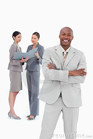 Smiling salesman with arms crossed and co-workers