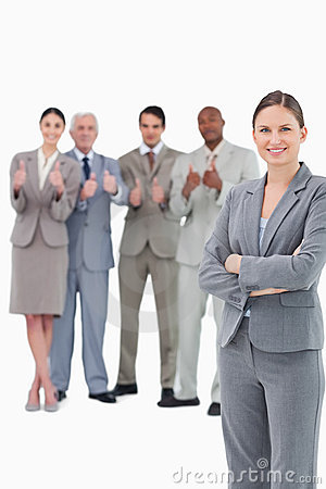 Smiling saleswoman with arms folded and her team behind her