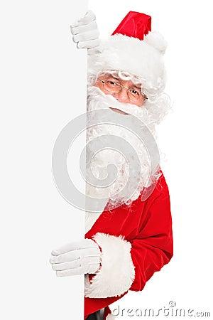 Smiling Santa Claus posing behind a blank panel