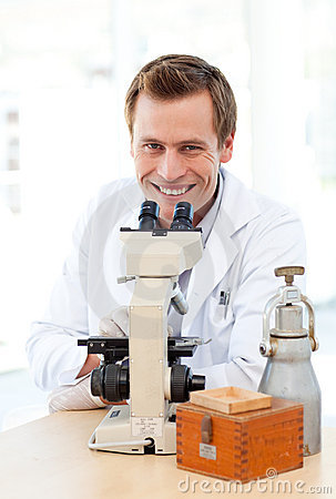 Smiling scientist looking through a microscope