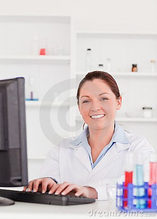 Smiling scientist typing a report