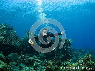 Smiling Scuba Diver descending on a Reef