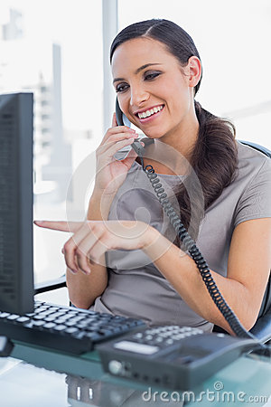 Smiling secretary answering land line and pointing at computer screen