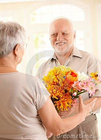 Smiling senior man bringing flowers