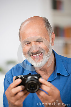Smiling senior man with a camera