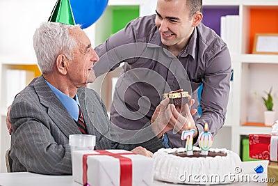 Smiling senior man receiving gift for birthday