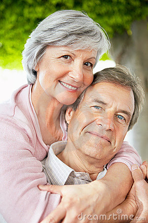 Smiling senior woman with arms around a man