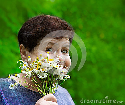 Smiling senior woman with field flowers