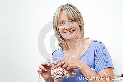 Smiling senior woman knitting