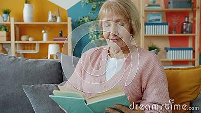 Smiling senior woman reading book sitting on couch at home enjoying novel. Smiling senior woman is reading book sitting on couch at home enjoying novel turning stock video