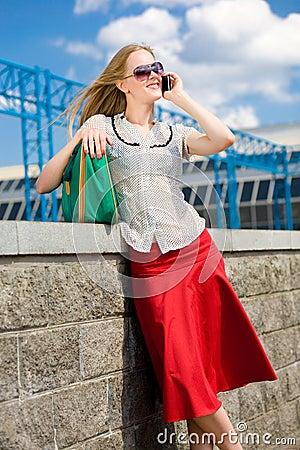 Smiling sexy blonde girl talking on phone