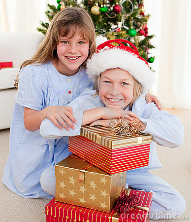 Smiling siblings holding Christmas gifts