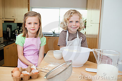 Smiling siblings preparing dough