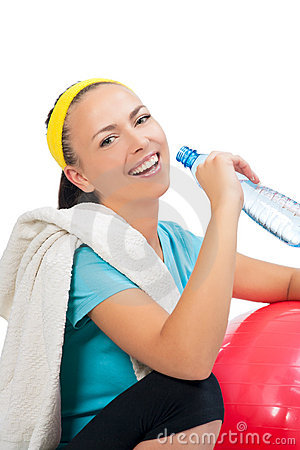 Smiling sportswoman drinking water after training