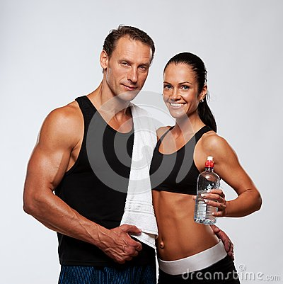 Smiling sporty man and woman with bottle